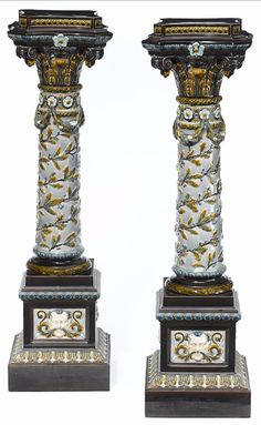 Continental majolica pedestals,  late 19th century, Corinthian capitals, above a column with cornucopia, garlands and leaf and berry vines, the stepped base having male masks. height 46 1/2in