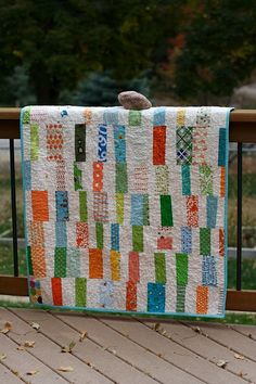 cot quilt- love the pop of greens, blues and oranges against a neutral background