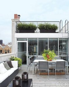 The main terrace of designer Cristina Azario's renovated brownstone in East Harlem, New York features a table and chairs by Design Within Reach.