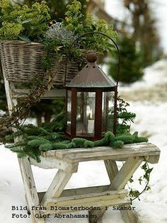 A simple lantern with greenery on a chair.