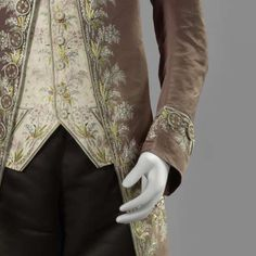 Detail, 3-piece suit, probably The Netherlands, 1775 - 1800. Liver-colored silk, richely embroidered with a floral motif in multicolored silk, fabric-covered and embroidered buttons; waistcoat: cream silk with similar embroidery; breeches: black silk satin, bands with similar embroidery.
