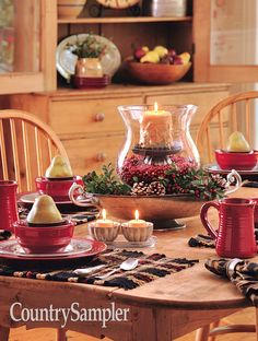 Put together a layered arrangement by tucking a large glass hurricane candleholder inside a silver serving bowl filled with pinecones and greenery. Within the hurricane, seat a decorative candleholder, anchoring it with cranberries. Coastal Christmas, Winter Christmas, Christmas Ideas, Christmas Crafts, Christmas Tables, Christmas Table Decorations, Holiday Decor, Country Sampler Magazine, Large Glass Jars