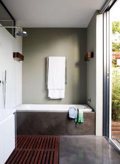 Une salle de bain en béton ciré version chic - la résine brillante et les nuances de ce gris chaud apporte une connotation moins industrielle que d'habitude. La peinture au mur s'harmonise très bien.