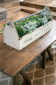 HGTV: This added centerpiece of greenery in an old wooden tool box adds extra flair to the coffee table in the living room.
