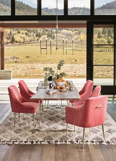 Open dining space with a low-hanging gold chandelier, pink armchairs, and a reclaimed wood table