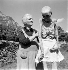 woman holding mummy scarecrow