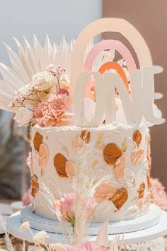 Check out the amazing boho rainbow birthday cake topped with flowers and a pretty cutout rainbow at this boho rainbow 1st birthday party! See more party ideas and share yours at CatchMyParty.com