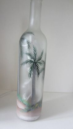 PALM TREES ON A FROSTED BOTTLE ***** HAND PAINTED PALM TREES This beautiful hand painted lighted bottle is 12 3/4 inches tall. It has a frosted finish to make the painting more vivid. This bottle is finished all the way around, with palm trees , sand and grass... As with all our