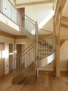 Stainless steel and oak stair leading to gallery overlooking main living space in house near Cardiff
