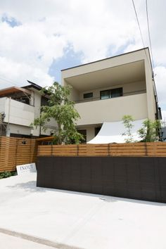 スクエアな外観の小林邸。黒の塀とウッドの組み合わせが効いている。日除けの帆布のタープは店で使っていたものだそうだ。