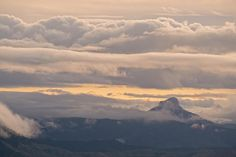 Mount Lindesay peeks out from the mist and cloud at sunset. #mountain #clouds #sunset #wallart #australia