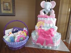 """DIY Diaper Cake:  - 26 newborn diapers (top)  - 30 second size diapers (middle)  - 64 third size diapers (bottom) - 6 x 4oz bottles - 12 washclothes  - 2 onsies  - Pamper wipes  - Johnson's travel pack (baby wash, baby shampoo, baby powder, 2 nursing pads, diaper cream)  - 2 pacifiers  - Chewing ring  - 6 pairs of socks  - Stuffed elephant  - OPI polish """"It's a Girl"""" (For her)  - Shot of whiskey (For him)    Easy and fun gift for the mother to be!"""
