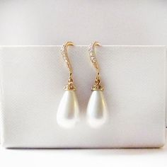 A gorgeous creamy white shell pearl tear drop on a gold cubic zircon encrusted hook. A modern elegant design. Very versatile, perfect for a bride or even as a gift for bridesmaid or mother of bride. Details: Material: 16k gold plated brass, cubic zircon Length: approx 1.25 inches  Earrings ONLY, Matching necklace available at extra cost. Material: gold plated brass, shell pearl  This item is in-stock and ready to ship  If you would like to place an order for additional quantities please…