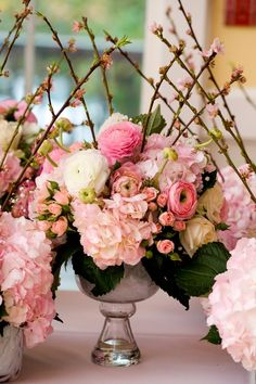 Lush pink centerpieces.  I really like the apple blossom branches; gives it a nice punch.  Ranunuculus, hydrangea, spray roses.
