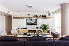 ¿Cómo ubicar la tele en el living? En este espacio en tonos claros, la TV va empotrada en el mueble central.