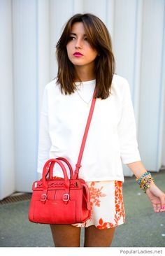 Printed shorts, white top and a red bag