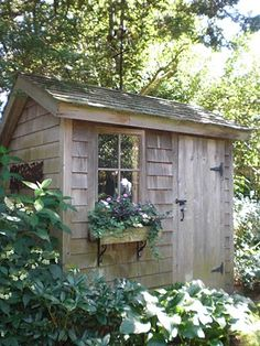 Garden shed made with a shingled exterior and old world hardware.
