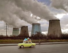 Picture of yellow car on highway with nuclear smoke stacks in background