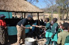 Children in our sponsorship program in Zimbabwe wait eagerly to receive their cereal.