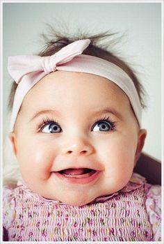Bebé menina com um sorriso encantador, umas bochechas grandes e um par de olhos azuis brilhantes