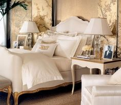 Layered cream coloured bedding on a gold framed French bed, set against a handpainted golden screen. A well designed room.