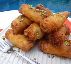 Znoud El Sit....Znoud el Sit are crispy on the outside and are filled with a thick clotted cream filling � fried to a golden brown crisp and dipped in sugar syrup infused with orange blossom water | Hadia's Lebanese Cuisine