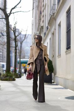 Camila Coelho during NYFW wearing a mix of prints with beautiful flare pants, a crop trop which ties in the front, and a geometric blazer in the same pattern with a caramel coat on top.  Look em tons neutros e com mix de estampas. Calça flare, um cropped com amarração e por cima um blazer na mesma estampa geométrica. Finalizei com um casaco caramelo over com listras e bolsa burgundy.