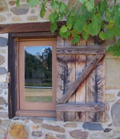 Beautiful old barn window at Lavandula Lavender Farm near Hepburn Springs, Victoria, Australia.  The reflection in the window shows a field of lavender growing surrounded by huge trees.
