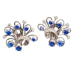 Sapphire Diamond Platinum Floral Spray Earrings. Designed as openwork platinum ribbon tied floral sprays, each is set with six oval and circular-cut sapphires and enhanced with nine small diamonds. The total weight of sapphires is approx 4.70 cts. Mounted as clips for easy wear.   1 1/8 x 1 in. (w x l) (2.9 x 2.5 cm)