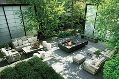 Grouped seating in a neutral palette, Chinese garden stools, shoji-inspired screens, bluestone pavers, and a sleekly modern fire pit make the side yard a serene space.