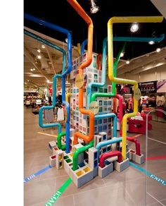 Creative, colorful, fun use of industrial materials for store display. Pipes and CMU blocks. Awesome.