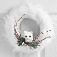 Bring wintertime whimsy to your decor with our glamorous, glittering wreath. Its ring of snowy white faux fur accented with real twigs and pinecones makes a posh perch for a handcrafted owl.