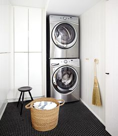 Laundry room features a silver stacked washer and dryer placed next to floor to ceiling cabinets alongside a black hex tiled floor.