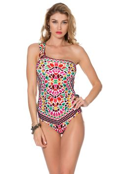 Asymmetrical one piece with removable soft cups, drop shelf, and strappy back. Features striped ring with beach shells and beads at strap.