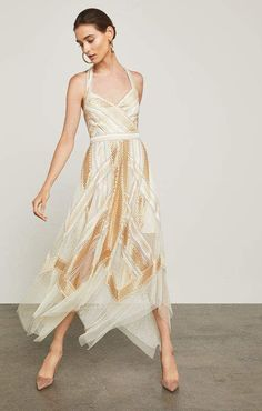 cb1384eab7e Create shimmering movement in this sleeveless alabaster gold halter dress  in metallic geo stripe embroidery on tulle that boasts a semi-sheer  handkerchief ...
