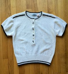 A 1980s short sleeve sweater top featuring a musical register on the front buttons! A white, light weave knit accented by black stripes on the shoulders, hem, neckline, and sleeve cuffs. the button front features four plastic pearl buttons, separated by musical notes and clef symbols. Ribbing at hem gives it that preppy, 80s feel. Totally nerdy in all the right ways.  Tag reads: JBJ Justin B. Jones. Size on tag: M Fit: Medium  In excellent vintage condition!  All measurements taken while…