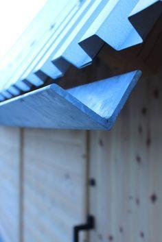 Functional steel profile roofing meets minimal metal angle as rainwater gutter on roof.