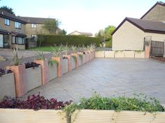 Sandstone and terracotta containers planted with variegated Phormium in the terracotta, red Heuchera and Vinca Minor in the Sandstone.    The wall was to give the children safe space to play while conforming to planning that said no immovable barrier.