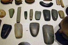 An array of Neolithic artifacts, including bracelets, axe heads, chisels, and polishing tools.These ground or polished implements are manufactured from larger-grained materials such as basalt, jade and jadeite, greenstone and some forms of rhyolite which are not suitable for flaking