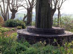 Wattle and daub tree trunk bench. Willow Fence, Willow Garden, Tree Seat, Tree Bench, Outdoor Rooms, Outdoor Gardens, Deck Around Trees, Wattle And Daub, Garden Terrarium