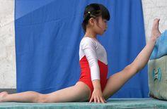片足を高い台に乗せて限界まで柔軟トレーニングをする体操少女
