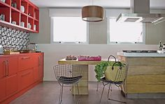A cozinha era muito longa e estreita, por isso a arquiteta Regina Adorno resolveu adotar uma ilha para a família preparar junto as refeições. A parede de ladrilho hidráulico estampado é a protagonista, junto ao móvel vermelho