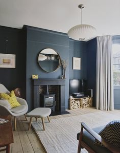 """The living room is painted in Dulux Raven Plume. """"I saved a bit of money by going with Dulux paint, and put the savings towards more expensive lighting,"""" says Julia. The pendant lamp is a George Nelson Saucer Bubble Pendant Light, which was designed by George Nelson in 1947 and first produced by Herman Miller in 1952. #dwell #homeextension #homerenovation #renovationideas #london #moderndesign #livingroom"""