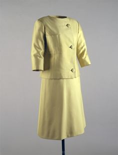 Yellow silk-and-wool Alaskine day suit, by Oleg Cassini, American, 1961. Worn by Jacqueline Kennedy on Easter Sunday, Palm Beach, Florida, April 2, 1961; also worn to luncheon with President and Madame de Gaulle, Elysee Palace, Paris, France, May 31, 1961; also worn to luncheon with Prime Minister Harold Macmillan, London, England, June 5, 1961; also worn at ceremony celebrating publication of the White House guidebook, the White House, Washington, DC, June 28, 1962.