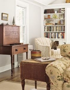 Living Room in a Farmhouse with Storybook Charm: Built-in shelves contain the overflow of books from the expansive barn library. Slipcovers and antique pieces, such as the writing desk by the window, lend the room a casual, lived-in appearance.   Photo: Country Living