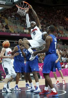 Team USA's first game of Olympics - Lebron James of the U.S. hangs on the basket after dunking the ball during the game against France during their men's Group A basketball match at the London 2012 Olympic Games in the Basketball arena July 29, 2012. REUTERS/Sergio Perez