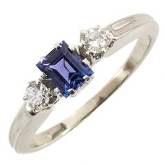 Sapphire Three Stone: We love the angular shape of this bright blue emerald cut sapphire and how it contrasts beautifully with the curves of two sparkling round diamond accents on either side of it. Maloys.com