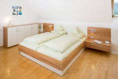 Moderner Schlafzimmereinbau aus Kernbuche mit weißen Lackelementen.