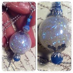 Witchball realized with a glass ball filled with angelina fiber Finished with filigree and blue agate Catch an reglect the light