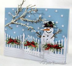cute snowy yard scene with snowman, fence decorated for Christmas and a tree with snow on its branches...